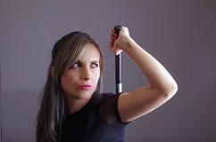 De samoeraienvrouw kleedde zich in zwarte die kleren houdend wapen over schouder het grijpen zwaard achter rug wordt verborgen, d Royalty-vrije Stock Fotografie