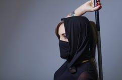 De samoeraienvrouw kleedde zich in zwarte met de aanpassing van sluier die gezicht behandelen, die wapen op zwaard houden dat ach Stock Afbeeldingen