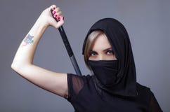 De samoeraienvrouw kleedde zich in zwarte met de aanpassing van sluier die gezicht behandelen, die wapen op zwaard houden dat ach Stock Foto