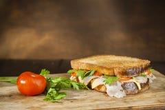 De sandwich en de tomaat met peterselie zijn op de oude raad Het snelle voedsel aan snack op gaat Stock Afbeeldingen