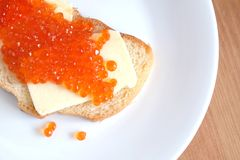 De sandwich met boter en rode kaviaar op wit brood ligt op witte ronde plaat op houten achtergrond Stock Foto