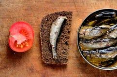 De sandwich met sprotten, gesneden tomaten en a kan van sprotten op Royalty-vrije Stock Afbeelding