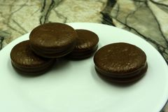 de sandwich van het chocoladekoekje in chocoladeglans op witte achtergrond wordt geïsoleerd die stock foto's