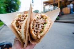 De sandwich van het close-up snelle voedsel op de straat in openlucht Actieve meisjes die hongerig en straatvoedsel na lange gang Stock Foto