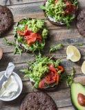 De sandwich van het roggebrood met roomkaas, gerookte zalm, arugula, stampte avocado op rustieke houten achtergrond, hoogste meni stock fotografie