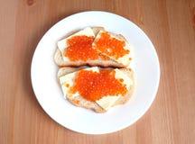 De sandwiches met boter en rode kaviaar op wit brood ligt op witte ronde plaat op houten achtergrond Stock Fotografie