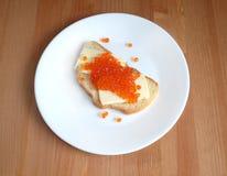 De sandwiches met boter en rode kaviaar op wit brood ligt op witte ronde plaat op houten achtergrond Royalty-vrije Stock Foto's