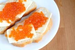 De sandwiches met boter en rode kaviaar op wit brood ligt op witte ronde plaat op houten achtergrond Royalty-vrije Stock Foto
