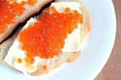 De sandwiches met boter en rode kaviaar op wit brood ligt op witte ronde plaat op houten achtergrond Stock Afbeeldingen