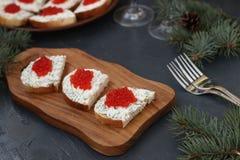 De sandwiches met rode kaviaar worden gevestigd op een houten raad royalty-vrije stock afbeeldingen