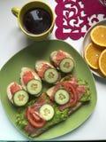 De sandwiches met zalm, groenten en greens liggen op een plaat Naast thee en fruit Stock Foto's