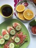 De sandwiches met zalm, groenten en greens liggen op een plaat Naast thee en fruit Royalty-vrije Stock Afbeelding