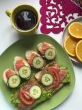 De sandwiches met zalm, groenten en greens liggen op een plaat Naast thee en fruit Stock Fotografie