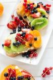 De sandwiches van het fruitdessert met ricottakaas, kiwi, abrikoos, aardbei, bosbes en rode aalbes Stock Afbeelding