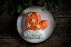 ` De Santa Claus Mitten del ` de la ensalada de salmones salados, de las patatas hervidas, del queso, de los huevos y de la carne Fotografía de archivo