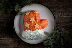 ` De Santa Claus Mitten del ` de la ensalada de salmones salados, de las patatas hervidas, del queso, de los huevos y de la carne Imagen de archivo