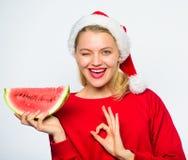 De santahoed van de meisjesslijtage eet de witte achtergrond van de plakwatermeloen De zomer behandelt op Kerstmispartij Exotisch royalty-vrije stock fotografie