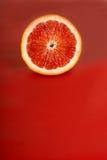 De sappige helft van een bloedsinaasappel op een rode achtergrond Stock Fotografie