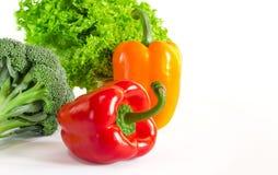 De sappige rode en oranje peper met een groene staart ligt naast Bundel van sla en de broccoli zijn op een witte achtergrond royalty-vrije stock afbeeldingen