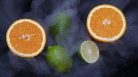 De sappige tropische vruchten sinaasappel en de kalk worden door een koude die stroom van lucht gekoeld bij hen wordt geleid stock video