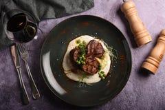De sappige varkensvleesmedaillons, dienen met groene erwten en een twijg van rozemarijn op een plaat De hoogste mening stock foto's