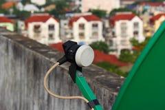 De satellietontvangersschotel is groen een dak. Stock Foto