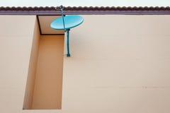 De satellietschotel installeert op de muur stock afbeelding