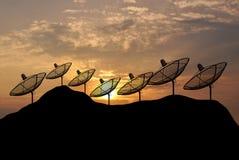 De Satellietschotel van het zonsondergangsilhouet op heuvel Royalty-vrije Stock Foto's