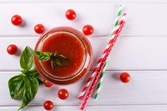 De saus van de tomatenketchup met kersentomaten en roodgloeiende Spaanse peperpeper, knoflook en kruiden in een glaskruik op witt Royalty-vrije Stock Foto