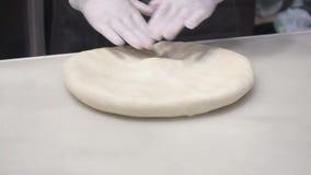 De sc?ne: De kok kneedt het deeg met zijn handen, vormend het deeg Productie van kaneelbroodjes De producten van de bakkerij stock videobeelden