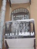 De scène van de de winterstad met ijskegels bij de bouw Huis faccade, balkon Stock Afbeeldingen