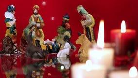 De scène van de Kerstmisgeboorte van christus met kaarsen op rood stock videobeelden