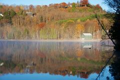 De scène van het de herfstplattelandshuisje met mist Stock Fotografie