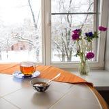 De scène van het de winterontbijt: kop thee, plaat met oranje jam Royalty-vrije Stock Foto