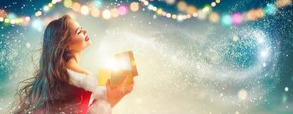 De scène van Kerstmis Schoonheids donkerbruine jonge vrouw in partijkostuum het openen giftdoos royalty-vrije stock foto
