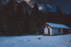 De scène van de de winternacht in de bergen, chalet in de bomen royalty-vrije stock afbeeldingen