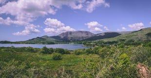 De sceniska fälten och havet som sett från vägen som leder till det Healy passerandet, från byn av Adrigole Arkivfoton