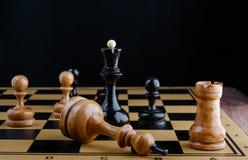 De schaakstukken worden geplaatst op het schaakbord Verslagen witte koning Stock Afbeeldingen