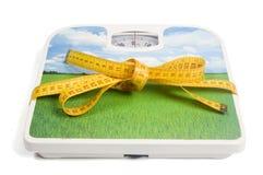 De schaal van het gewicht met een maatregelenband als lint Stock Fotografie