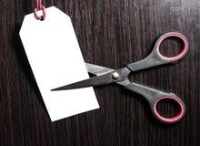 De schaar sneed document wit prijskaartje op een bruine houten achtergrond voorraad kortingen voordeel Het concept van de marketi Stock Afbeelding
