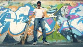 De schaatser bevindt zich dichtbij een straatmuur en heft zijn raad door zijn been op stock videobeelden