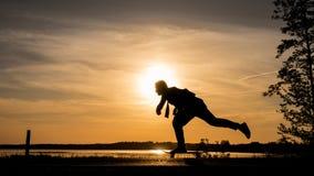 De schaatser op weg maakt wijd het duwen tegen de zonsondergang stock foto