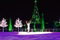 De schaatser van de vrouwenkunstenaar presteert op ijs bij Kerstmis toont op Internationaal Aandrijvingsgebied stock afbeelding