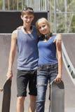 De schaatsers van de tiener met raad in skatepark Stock Foto's