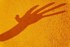 De schaduw van de hand die op texturized gele muur wordt vervormd Stock Foto