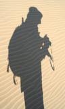 De schaduw van de ontdekkingsreiziger in zand, Nam stock afbeeldingen