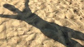 De schaduw van een mens in het zand stock video