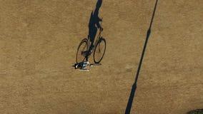 De schaduw van fiets en ruiter beweegt zich langzaam in het park Ongebruikelijke mening vanaf bovenkant stock video
