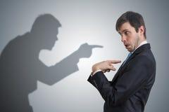 De schaduw van de mens richt en beschuldigt zakenman Gewetensconcept stock afbeelding