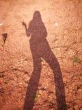 De schaduw van de vrouw op de droge kleioppervlakte van de grond stock afbeeldingen